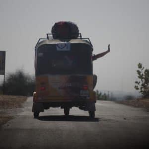 Waving out of a rickshaw