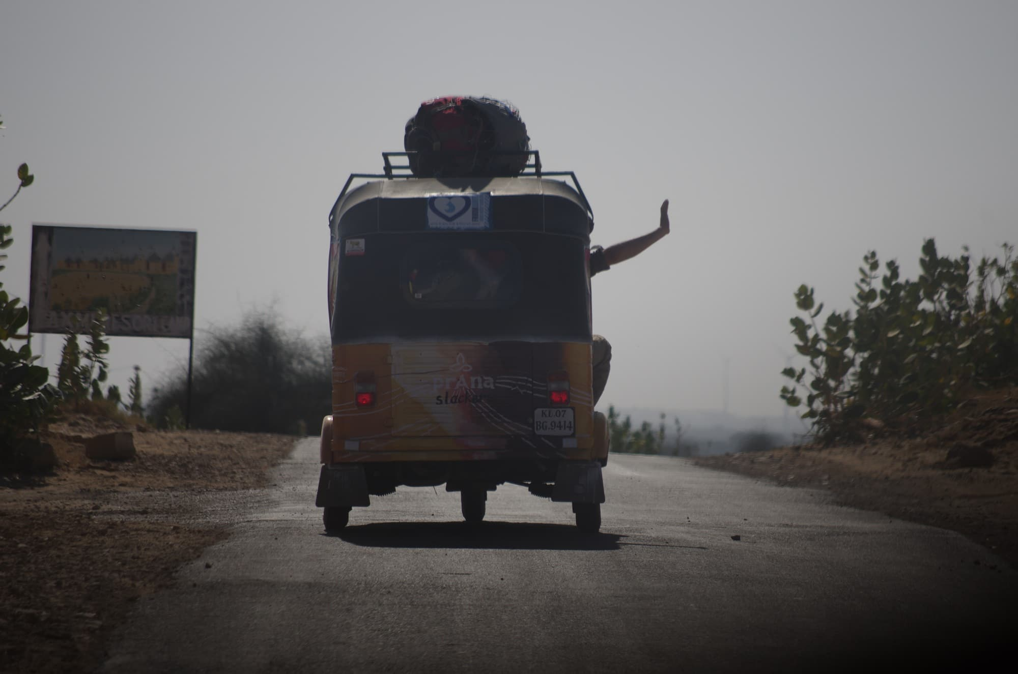 Waving out of a rickshaw